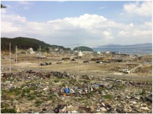 南三陸町。志津川湾から続く平地部分は建物のほぼすべてが壊滅しており、移動する自動車以外に人の姿は見えない。右上方向が海