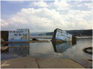 決壊した堤防。「青い海 みんなで守る 思いやり」「汚すまい この海この浜 この港」堤防にはこんな標語が書いてある